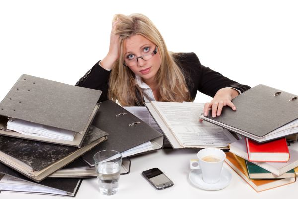 Woman struggling on papers, books and work